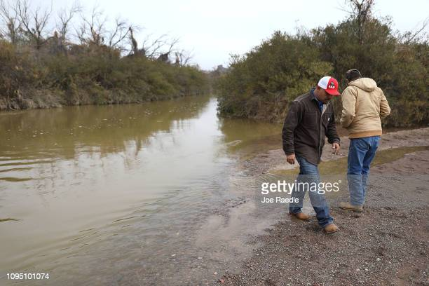 Adan Madrid and his father Adan Madrid sr walk together on their ranch land next to the Rio Grande river which marks the border between Mexico and...