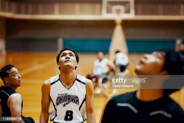 adapted athletes playing a game of wheelchair basketball - バスケットボールのユニフォーム ストックフォトと画像