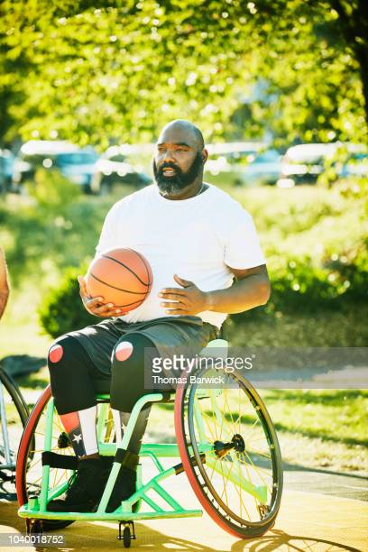 Adaptive athlete at wheelchair basketball practice on outdoor court on summer evening