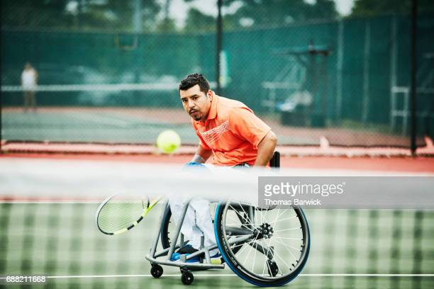 adaptive athlete chasing down shot during wheelchair tennis match - racquet stock pictures, royalty-free photos & images