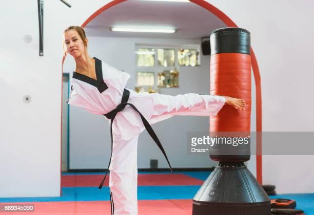 Adaptative athlète faisant le coup de pied arrière pour le sac de boxe
