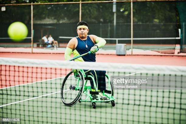 Adaptive athlete making forehand shot during wheelchair tennis match