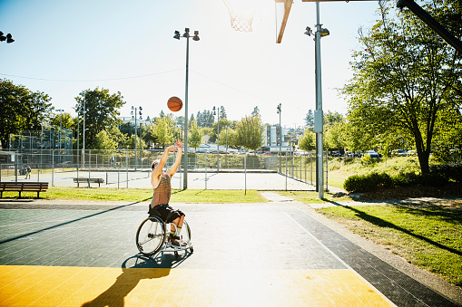 Adaptive athlete playing basketball on outdoor court on summer afternoon - gettyimageskorea