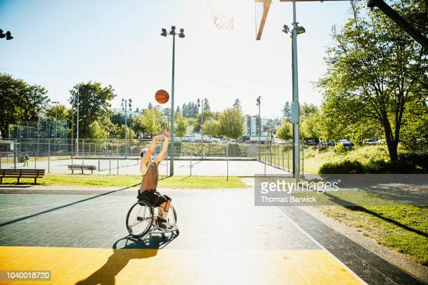 adaptive athlete playing basketball on outdoor court on summer afternoon - drive ball sports stock pictures, royalty-free photos & images