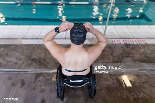 adaptive athlete prepares to swim in a pool - paraplegic stock photos and pictures