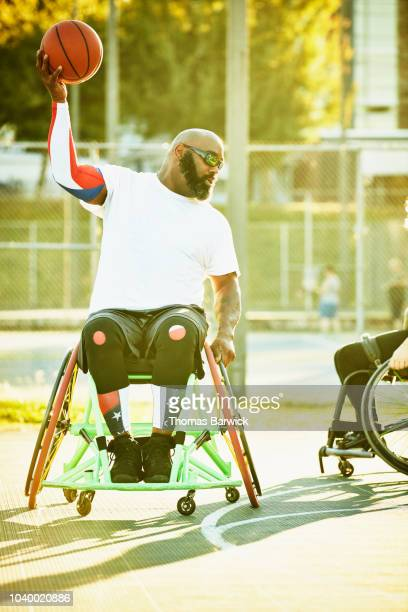 Adaptive athlete preparing to pass ball during wheelchair basketball game on summer evening