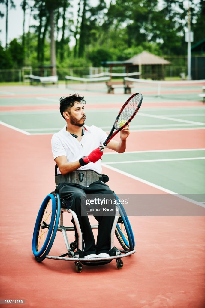 Adaptive athlete preparing to serve while playing wheelchair tennis : Stock Photo