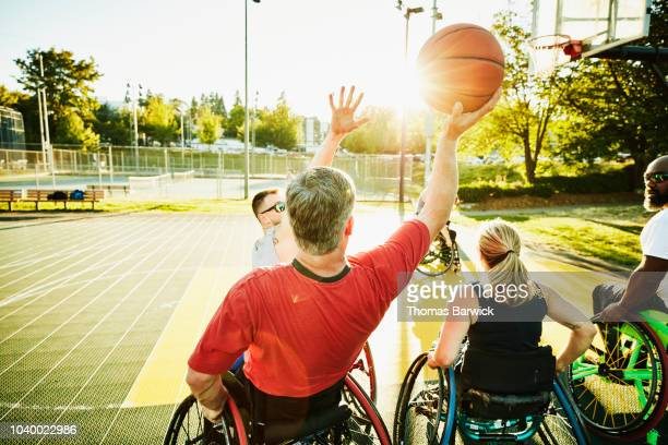 Adaptive athlete preparing to shoot ball during wheelchair basketball game on summer evening