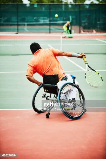 adaptive athlete serving during wheelchair tennis match - 車いすテニス ストックフォトと画像