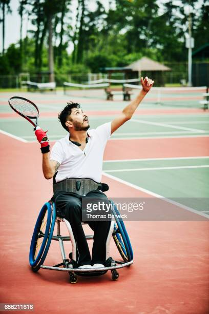 Adaptive athlete serving while playing wheelchair tennis