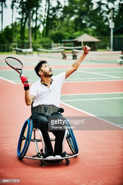 adaptive athlete serving while playing wheelchair tennis - saque deporte fotografías e imágenes de stock