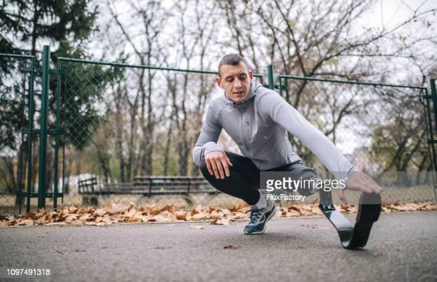 adaptive athlete stretching before training - pessoas com deficiência imagens e fotografias de stock