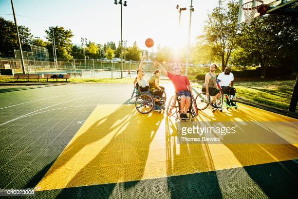adaptive athlete taking shot during wheelchair basketball game on outdoor court - physical disability stock pictures, royalty-free photos & images