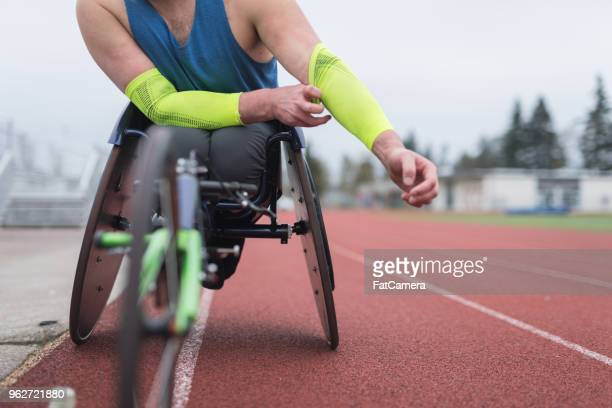 Adaptive athlete training on his racing wheelchair at a stadium track