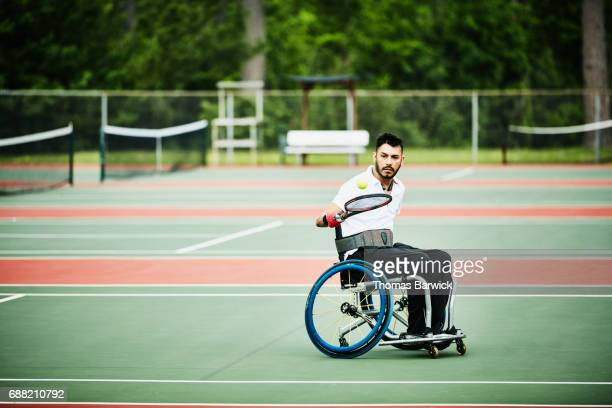adaptive athlete warming up for wheelchair tennis match - racquet stock pictures, royalty-free photos & images