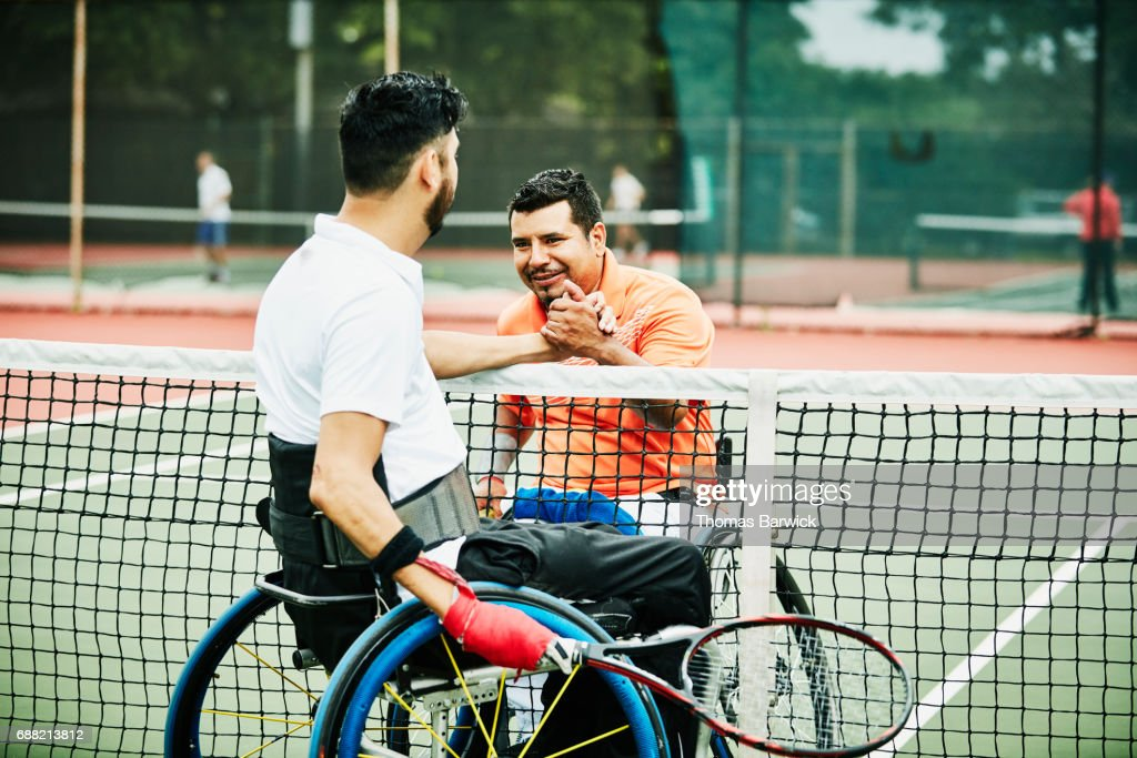 Adaptive athletes shaking hands at net after wheelchair tennis match : Stock Photo