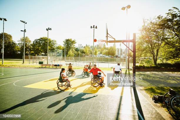 Adaptive athletes warming up for basketball practice on outdoor court on summer afternoon