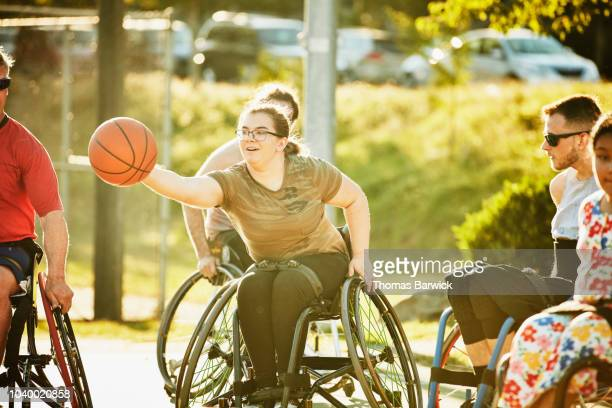 adaptive female athlete stretching for ball during wheelchair basketball game on summer evening - basketball sport stock pictures, royalty-free photos & images
