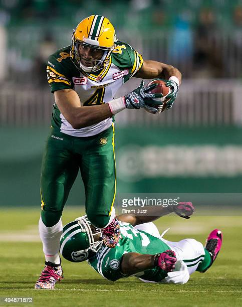 Adarius Bowman of the Edmonton Eskimos escapes from the grasp of Tristan Jackson of the Saskatchewan Roughriders after making a catch in the game...