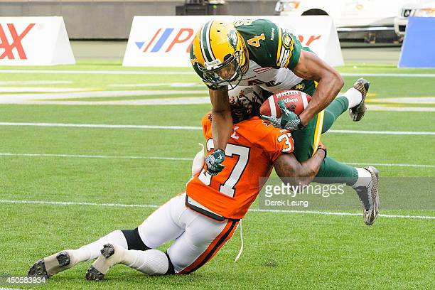 Adarius Bowman of the Edmonton Eskimos gets stopped by Ronnie Yell of the BC Lions during a CFL game at Commonwealth Stadium on June 13 2014 in...