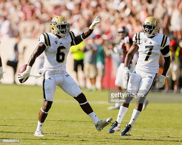 Adarius Pickett of the UCLA Bruins celebrates his interception with Darren Andrews in the third quarter against the Texas AM Aggies at Kyle Field on...