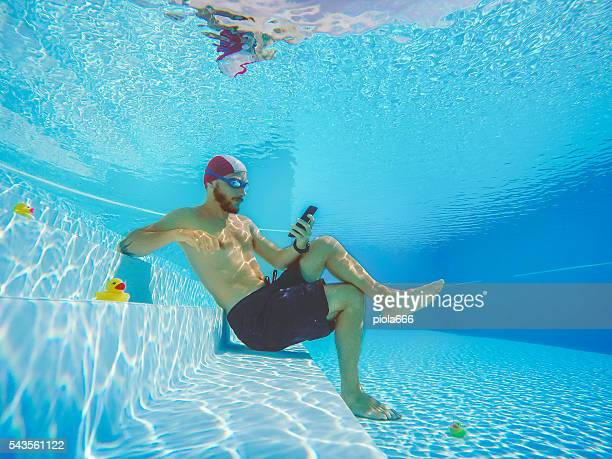 addicted to social networking: with mobile phone underwater - enslaved stock pictures, royalty-free photos & images
