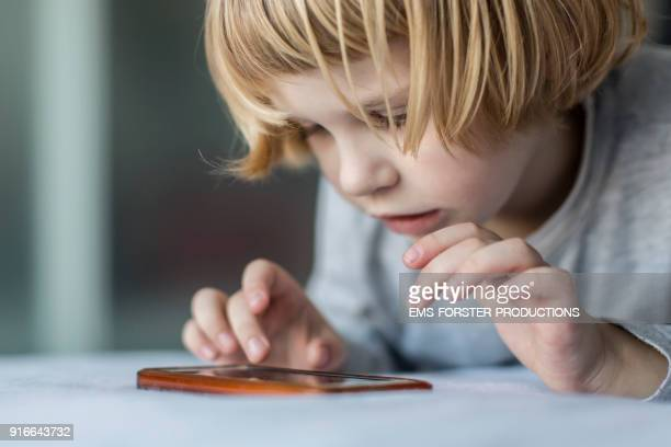 addictive , little boy is playing with mobile phone in bed