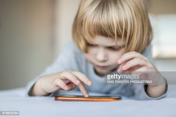 addictive, young boy is playing with mobile phone in bed