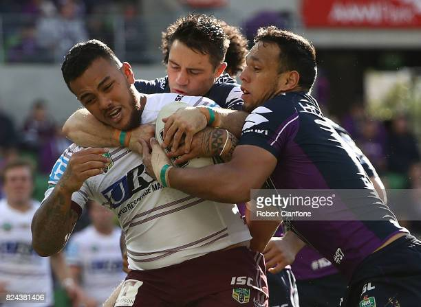 Addin FonuaBlake of the Sea Eagles is tackled by Will Chambers and Cooper Cronk of the Storm during the round 21 NRL match between the Melbourne...
