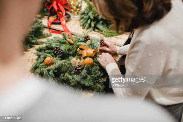 adding decorations to her christmas wreath - wreath stock pictures, royalty-free photos & images