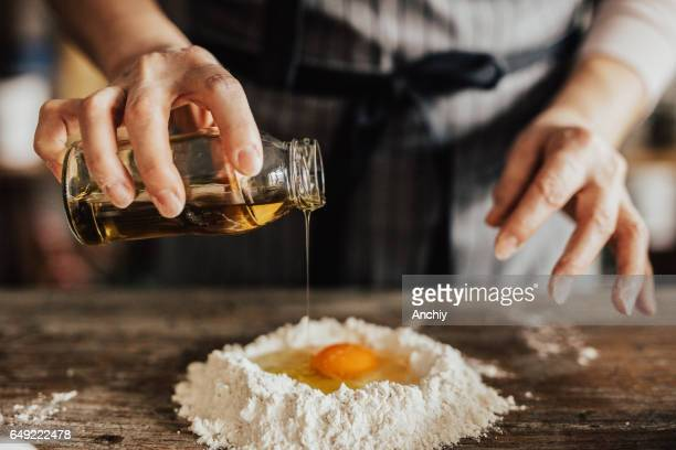 Adding oil to the egg and flour