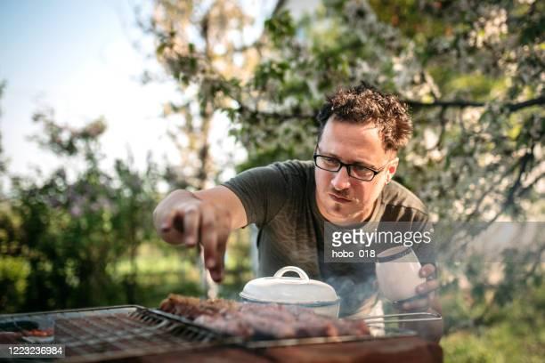 より良い味のために調味料のピンチを追加します - 網焼き ストックフォトと画像