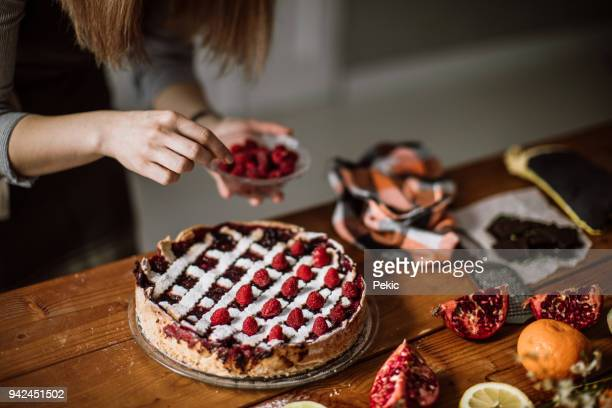 adding raspberries to tasteful blackberry pie - cake decoration stock pictures, royalty-free photos & images