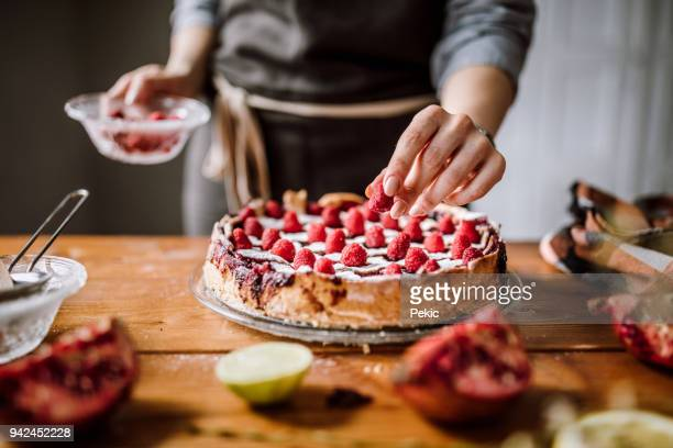 adding raspberries to tasteful blackberry pie - ornato foto e immagini stock
