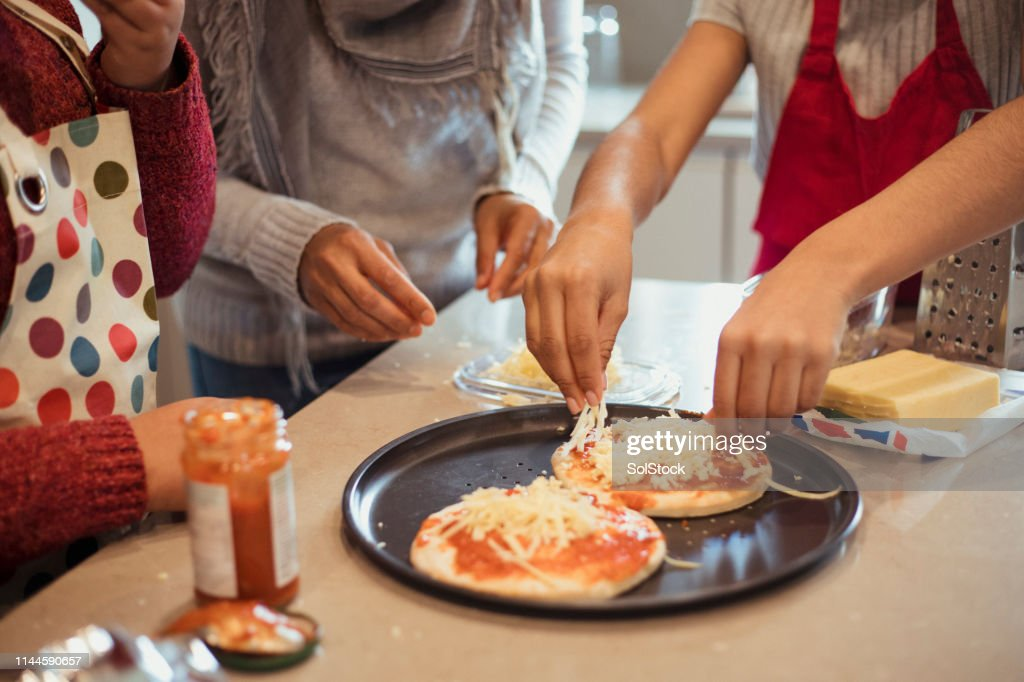Adding the Toppings to the Pizza : Stock Photo
