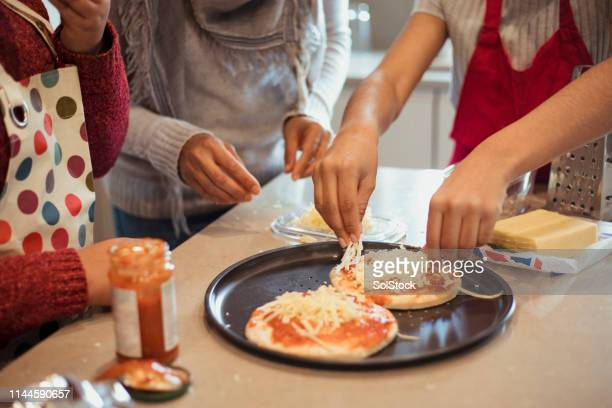 adding the toppings to the pizza - 40 44 jaar stock pictures, royalty-free photos & images