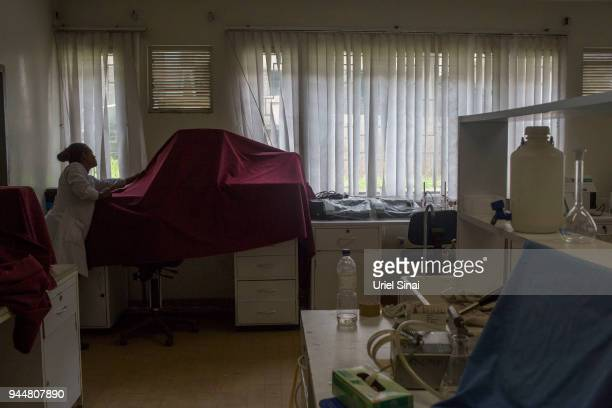 A laboratorian covers a biomedical laboratory equipment as it sits unplugged at the Addis Ababa university on September 25 2015 in Addis Ababa...