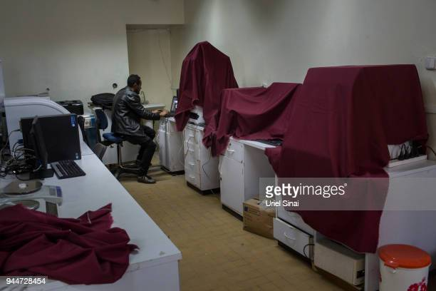 A PHD student works on his computer as state of the art biomedical laboratory equipment sits unplugged and covered with sheets at the Addis Ababa...