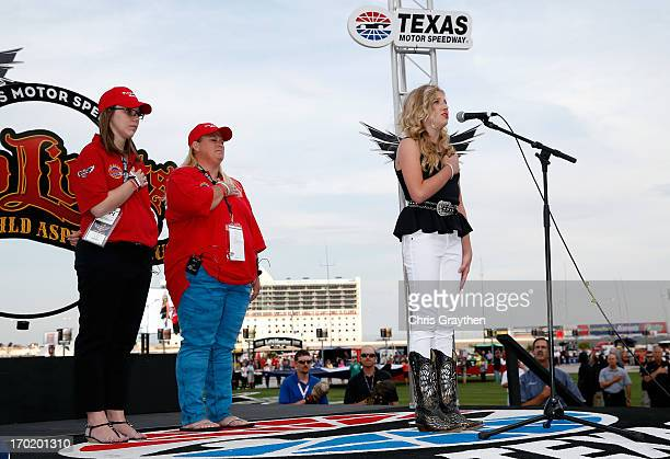 Addison Baker signs the national anthem as CoGrand Marshals Jennifer Simonds and Anna 'Sam' Canaday school teachers from Plaza Towers Elementary...