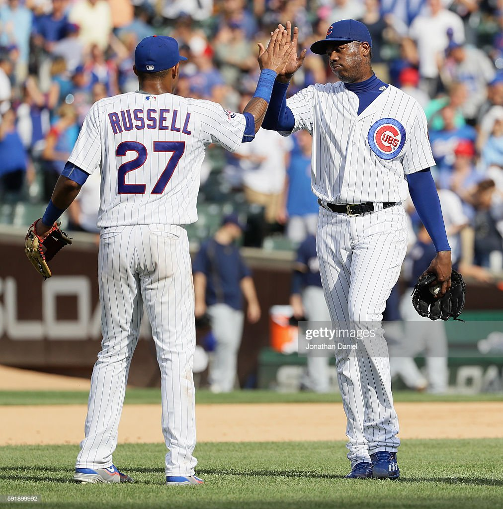 Addison Russell #27 and Aroldis Chapman #54 of the Chicago Cubs celebrate a win over the Milwaukee Brewers at Wrigley Field on August 18, 2016 in Chicago, Illinois. The Cubs defeated the Brewers 9-6.