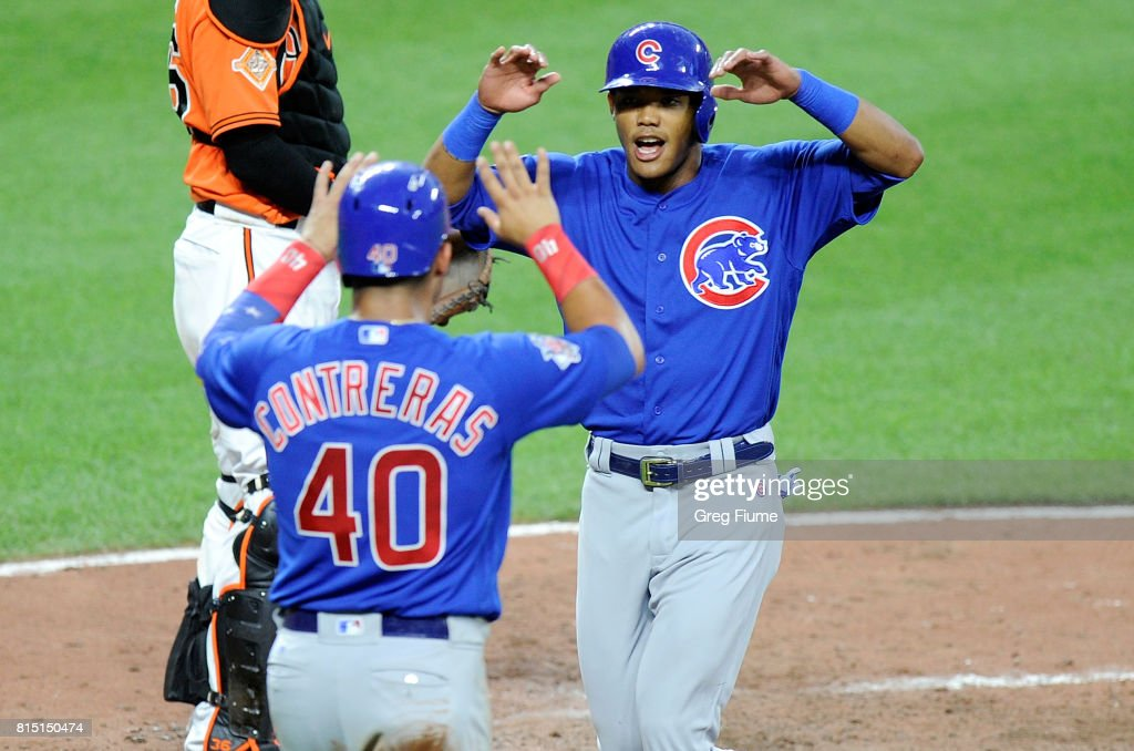 Addison Russell #27 and Willson Contreras #40 of the Chicago Cubs celebrate after scoring in the fifth inning against the Baltimore Orioles at Oriole Park at Camden Yards on July 15, 2017 in Baltimore, Maryland.