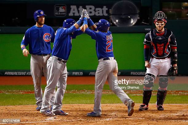 Addison Russell of the Chicago Cubs celebrates with Kyle Schwarber and Ben Zobrist after hitting a grand slam home run during the third inning...