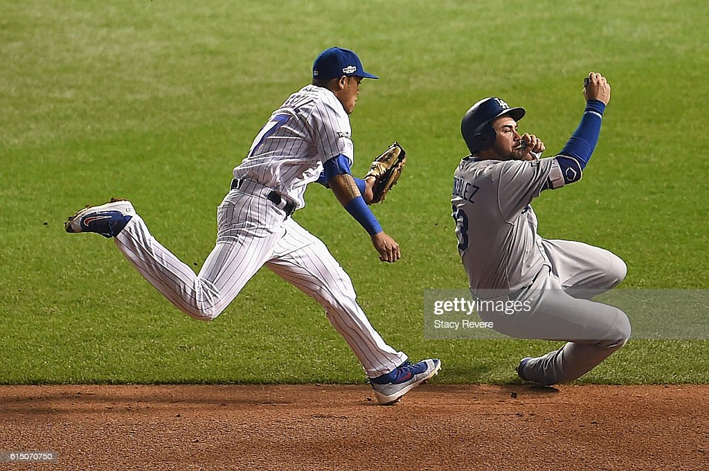 Addison Russell #27 of the Chicago Cubs chases Adrian Gonzalez #23 of the Los Angeles Dodgers in the sixth inning before tagging him out to complete the double play during game two of the National League Championship Series at Wrigley Field on October 16, 2016 in Chicago, Illinois.