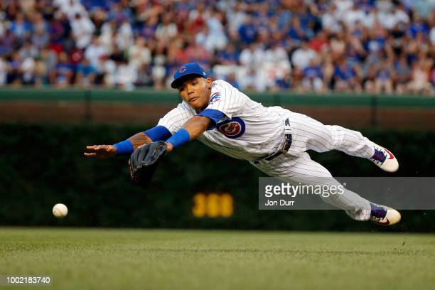 Addison Russell of the Chicago Cubs dives and is unable to field a ball hit by Yadier Molina of the St Louis Cardinals during the fifth inning at...
