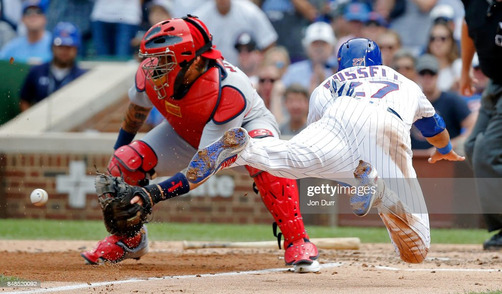 Addison Russell #27 of the Chicago Cubs dives home to score on an RBI single by Ben Zobrist #18 (not pictured) as Yadier Molina #4 of the St. Louis Cardinals is unable to make the catch during the fourth inning at Wrigley Field on September 17, 2017 in Chicago, Illinois.