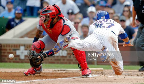 Addison Russell of the Chicago Cubs dives home to score on an RBI single by Ben Zobrist as Yadier Molina of the St Louis Cardinals is unable to make...