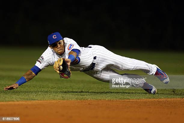 Addison Russell of the Chicago Cubs dives to catch a Tyler Naquin of the Cleveland Indians line drive in the third inning during Game 3 of the 2016...