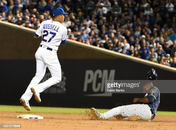 Addison Russell of the Chicago Cubs forces out Lorenzo Cain of the Milwaukee Brewers at second base and throw to first base to complete a double play...