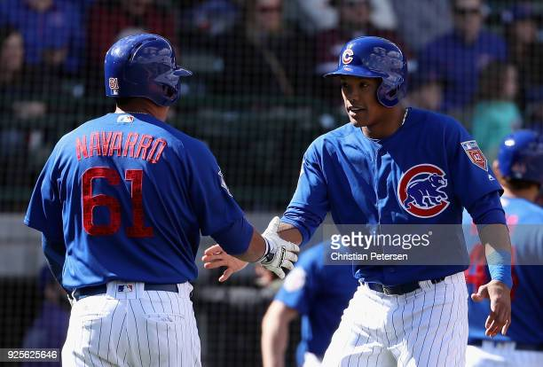 Addison Russell of the Chicago Cubs high fives Efren Navarro after scoring against the Oakland Athletics during the third inning of the spring...