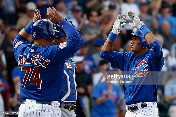 Addison Russell of the Chicago Cubs highfives Dan Vogelbach after Russell hit a tworun home run against the Kansas City Royals during the fifth...